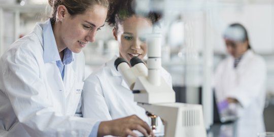 Female Scientists Beside A Microscope